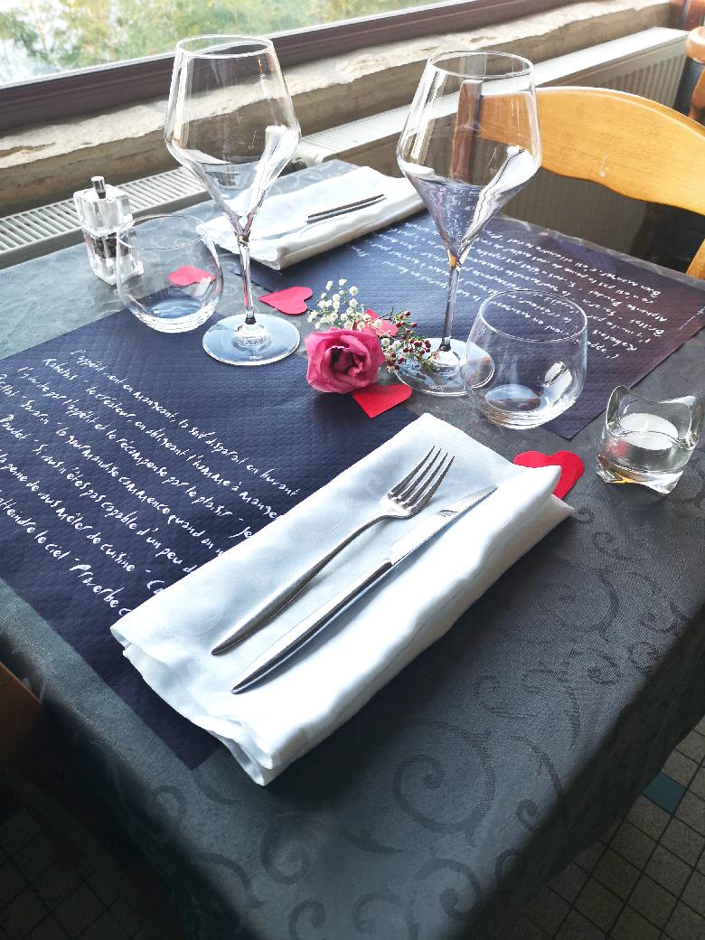 Table de restaurant avec set de table en papier noir inscription de proverbe blanc accompagnée de 2 verres et 2 verre à eau